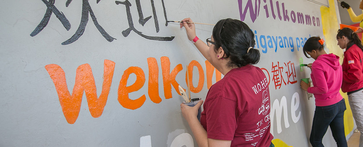 Students painting a wall with Welcome written on it in various languages